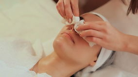Wiping the face with wet wipes. Cosmetic procedures Mechanical cleaning of the face. Cosmetology. stock footage