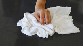Wiping stone counter. Woman's hand with cotton terry towel wiping stone counter Stock Images