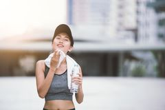 Wiping sweat Thirsty exercising female drinking fresh water after training royalty free stock image
