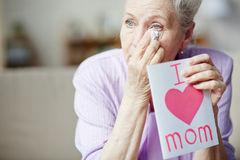 Wiping tears. Elderly woman with greeting card wiping tears Royalty Free Stock Photo