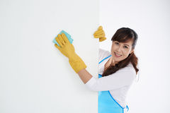 Wiping wall. Asian woman wiping white wall with wet cloth Stock Photo