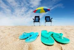 Wipschakelaars, ligstoelen en zonparaplu op strand Royalty-vrije Stock Foto