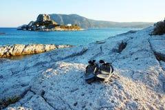 Wipschakelaars/Pantoffels die op klip dichtbij het overzees liggen Royalty-vrije Stock Afbeeldingen