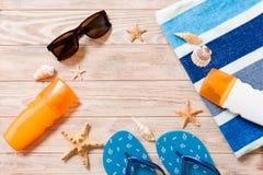 Wipschakelaars, strohoed, zeester, zonneschermfles, de nevel van de lichaamslotion op houten hoogste mening als achtergrond vlak  stock afbeelding