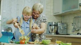 Wir arbeiten zusammen Das Mädchen von 6 Jahren zusammen mit der Großmutter tun einen Salat in der Küche, haben eine gute Zeit Ges stock video footage