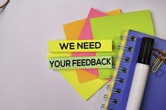 Wir benötigen Ihr Feedback auf den klebrigen Anmerkungen, die auf weißem Hintergrund lokalisiert werden stockfoto