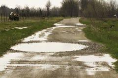 Żwir droga z kałużami i wybojami fotografia royalty free