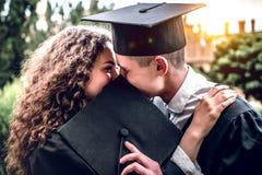 Wir gehen zusammen in Erwachsensein Ein liebevolles Paar von Absolvent küssen stockfoto