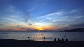 Wir grüßen die Dämmerung auf dem Ufer des warmen Meeres Lizenzfreie Stockfotos