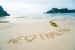 Wir lieben Thailand - simsen Sie eigenhändig geschrieben in Sand auf einen Seestrand mit Kajak über Himmel Lizenzfreies Stockfoto