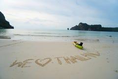 Wir lieben Thailand - simsen Sie eigenhändig geschrieben in Sand auf einen Seestrand mit Kajak über Himmel Stockfoto