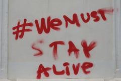 Wir müssen lebendig bleiben, Spritzpistolenzitat auf einer Wand von Bukarest stockfoto