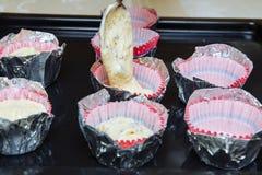 Wir schlugen die kleinen Kuchen zu Hause In der Papierform den Teig auferlegen lizenzfreie stockfotografie