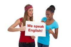 Wir sprechen Englisch - zwei Frauen, die auf Weiß lokalisiert werden stockbilder
