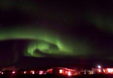 Wirbelnde Aurora Borealis über einer Kleinstadt in Nord-Island lizenzfreies stockbild