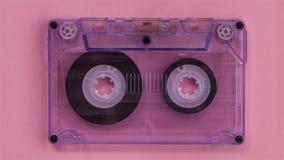 Wirbelndes Band der Retro- Musikvertrags-Kassette auf rosa Hintergrund stock footage