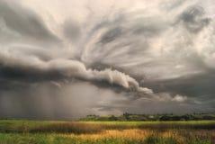 Wirbelsturmsturm über Feldern und Wiesen nähert sich dem hügeligen Tal Regnerischer bewölkter Tag lizenzfreies stockfoto