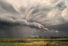 Wirbelsturmsturm über Feldern und Wiesen nähert sich dem hügeligen Tal Regnerischer bewölkter Tag lizenzfreie stockbilder
