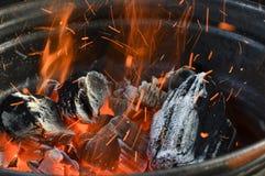 Wirbelwind funkt über den brennenden Kohlen in einer Scheibe von einem Rad Lizenzfreies Stockfoto