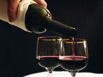 Wird in Rotwein des Weinglases gegossen Stockfotos