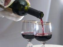 Wird in Rotwein des Weinglases gegossen Stockbild
