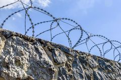 Sky and barbed wire on a stone fence stock photo