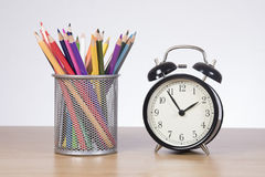 Wire basket with colored pencil crayons and alarm. Wire basket with colored pencil crayons and old-fashioned bell alarm clock on a wooden desk in a conceptual Stock Image