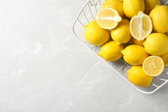 Wire basket with lemons. On gray table, top view royalty free stock image