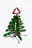Wire and bead Christmas Tree. A miniature Christmas Tree made of wire and beads, a craft practised by informal workers in South Africa. It has bright red and Stock Photo