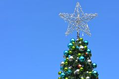 Wire Christmas star on tree. Top of traditional Christmas conifer tree with wire star covered with tiny lights with bright blue sky as background royalty free stock photos
