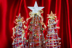 Wire Christmas Trees on Red Background. Wire Christmas Trees with Decorations on Red Drapery Background Stock Images