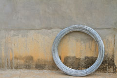 Wire. Circle wire on concrete wall background Stock Image