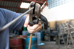 Wire clamp with black rubber handle in man hand. In factory Stock Photo