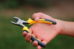 Wire Cutters. A close up view of a hand holding open some wire clippers Royalty Free Stock Image