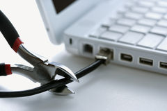 Wire Cutters Cutting Cable to Laptop Royalty Free Stock Photos