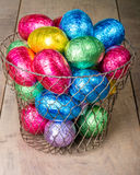 Wire egg basket with colorful eggs Royalty Free Stock Image