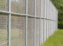 Wire Fence. A tall wire fence containing a sports field Stock Photography