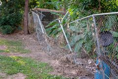 Wire Fence Damaged By Flood Waters. A wire mesh fence damaged by flood waters and a build up of debris stock images