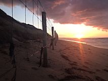 Wire fence at dawn. A wire fence on the beach at dawn stock photography