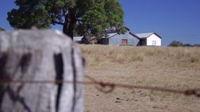 Wire fence with farm sheds pull focus