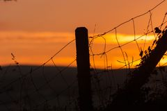 Fence Silhouetted Against Sunset. A wire fence with fence post silhouetted against a red sky at sunset Stock Photography