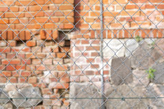 Wire fence in front of brick wall. Royalty Free Stock Photos