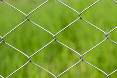 Wire fence on green grass background Royalty Free Stock Images