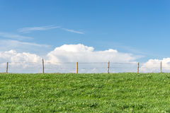 Wire fence on green grass field, blue sky, white clouds Stock Photography