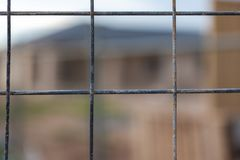 A wire fence with a selectively blurred background of a housing. Development in South Australia on 29th August 2018 stock images