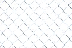 Wire fence in the snow. Fence background. Metallic net with snow. Metal net in winter covered with snow. Wire fence closeup. Steel. Wire mesh fence vintage stock photo