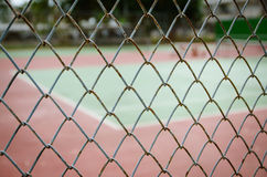 Wire fence with tennis court on background Stock Image