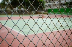 Wire fence with tennis court on background Royalty Free Stock Images