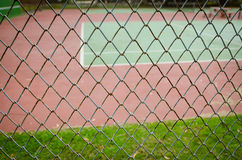 Wire fence with tennis court on background. Wire iron fence with tennis court on background Royalty Free Stock Photo