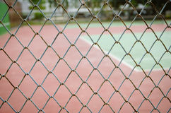 Wire fence with tennis court on background Royalty Free Stock Photography